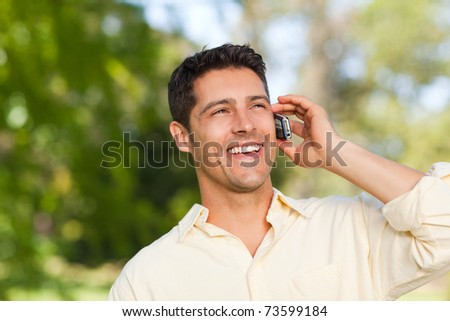 Man phoning in the park - stock photo