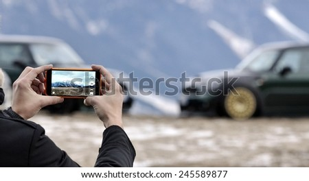 Man photographed mountains and parking cars in the new generation smart phone with snowy background in winter time. - stock photo