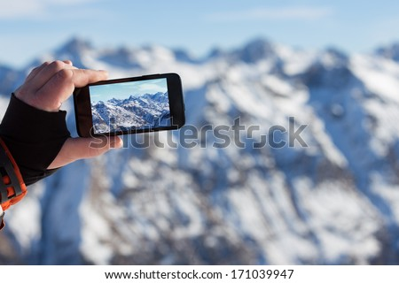 man photographed mountains in the smartphone - stock photo