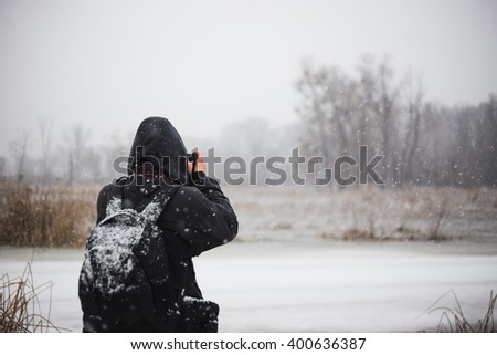 Man photographer taking picture on digital camera at outdoor in the winter Is snowing and man is enjoying the beautiful winter view.  - stock photo