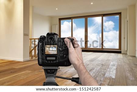Man photographing empty living room with digital camera - stock photo