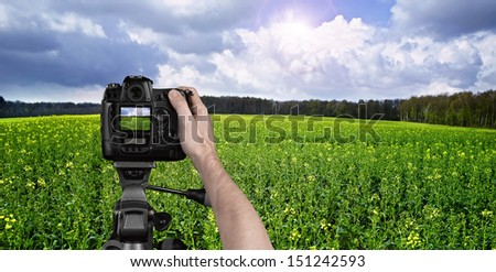 Man photographing landscape with digital camera - stock photo