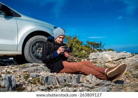 Man photographing lanscapes sitting near his car on the rocky mountain - stock photo