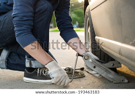 Man picks up a car jack to change a tire - stock photo