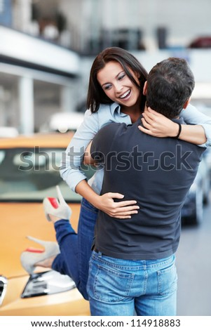 Man picks up on hands of a girl at the car - stock photo