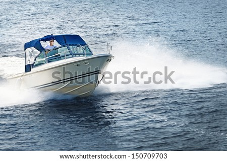 Man piloting motorboat on lake in Georgian Bay, Ontario, Canada. - stock photo