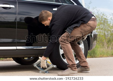 Man placing a hydraulic jack under his car to raise the vehicle allowing him to change the wheel for a spare following a roadside puncture - stock photo