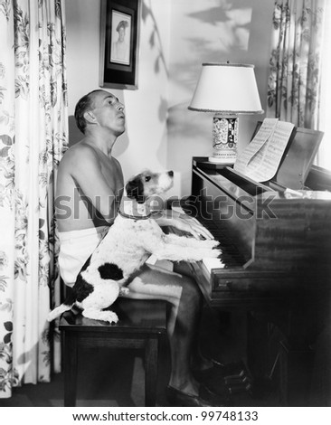 Man playing a piano with his dog next to him - stock photo
