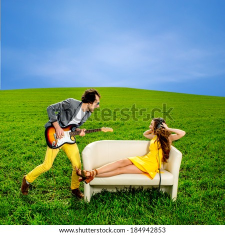 Man playing a solo on the guitar with girl lying on the couch and singing together on the green field - stock photo