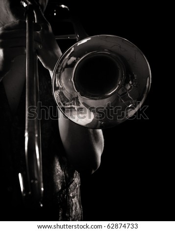 man playing a trombone, strong contrasting side-light, monochrome version - stock photo