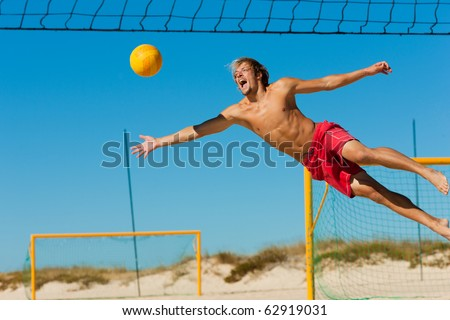 Man playing beach volleyball diving after the ball under a clear blue sky - stock photo