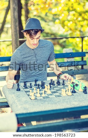 Man Playing Chess. Dressing in a gray long sleeves with roll-tab Henley shirt, wearing a woolen Fedora hat, a young handsome guy is playing chess outside in golden autumn afternoon. - stock photo