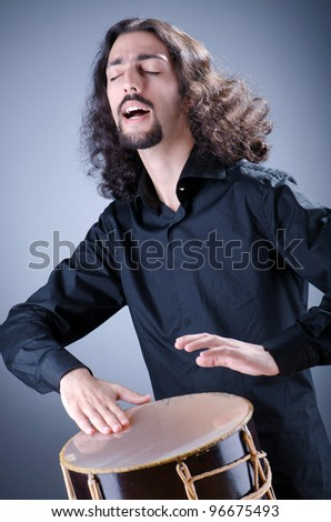 Man playing drum in studio - stock photo