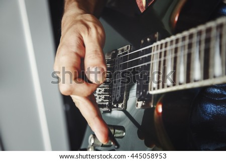 man playing electric guitar close up view, very shallow depth of field image, cinematic effect applied - stock photo