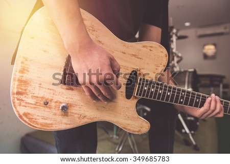 man playing electrical guitar in vintage tone style,music studio - stock photo