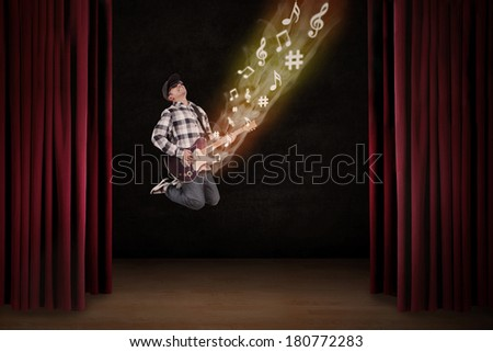 Man playing electrical guitar jumping on a stage - stock photo