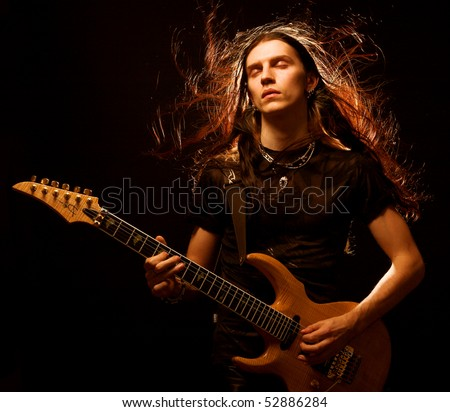 man playing electrical guitar. wind in hair. - stock photo