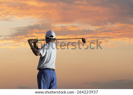 Man playing golf against sunset - stock photo
