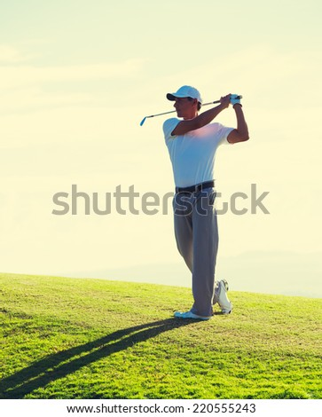 Man Playing Golf on Course Early Morning at Sunrise - stock photo