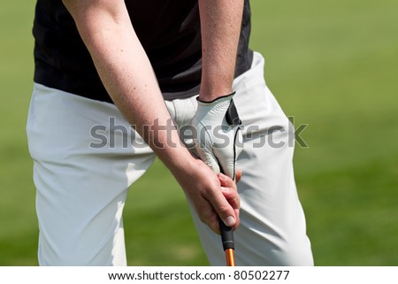 man playing golf while wearing a blue polo and white trousers - stock photo