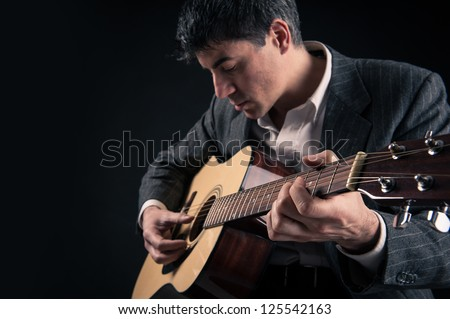 Man playing guitar against black background. Focus on hand. - stock photo