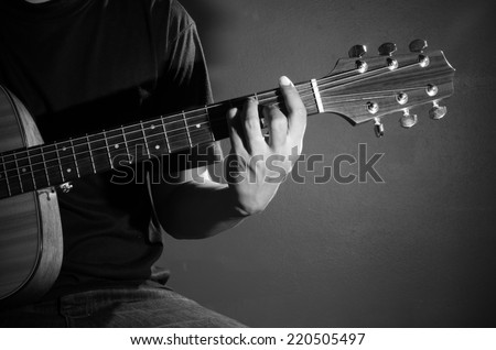 Man playing guitar. Black and white photo. - stock photo