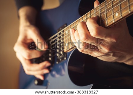 Man playing guitar close-up shot - stock photo