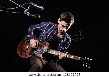Man playing guitar during concert - stock photo