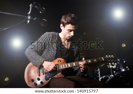 Man playing guitar during concert - stock photo