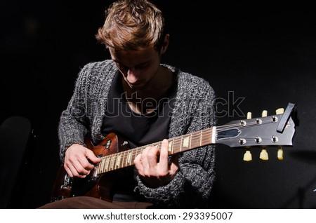Man playing guitar in dark room - stock photo