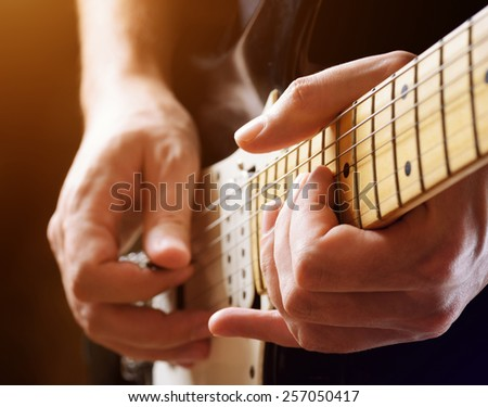 Man playing guitar on a stage. Close-up view. Live rock stars performing musical hits. Guitar solo in the spotlight. Musician pluck the strings with the help of a plectrum in light of the footlights. - stock photo