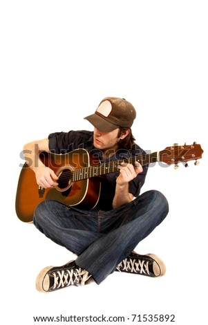 man playing his acoustic guitar seated on white background - stock photo
