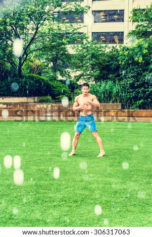 Man Playing in Rain, foggy, wet, grainy feel. Shirtless, half naked, wearing blue shorts, barefoot, a young sexy guy standing, exercising on green lawn in New York, enjoying raining day in hot summer. - stock photo