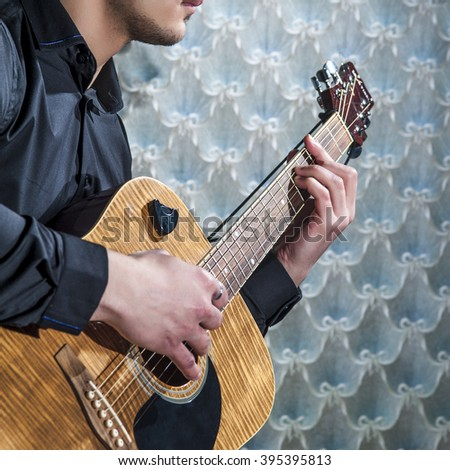Man playing on acoustic guitar, closeup. - stock photo