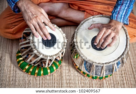 Man playing on traditional Indian tabla drums close up - stock photo