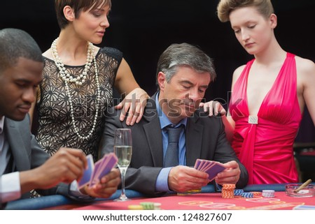 Man playing poker with two women beside him in casino - stock photo