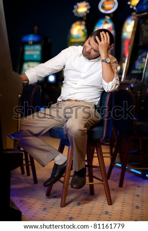 man playing slot machine in a night casino, bored - stock photo