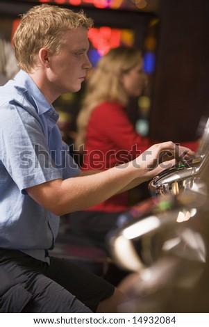 Man playing slot machines in casino - stock photo