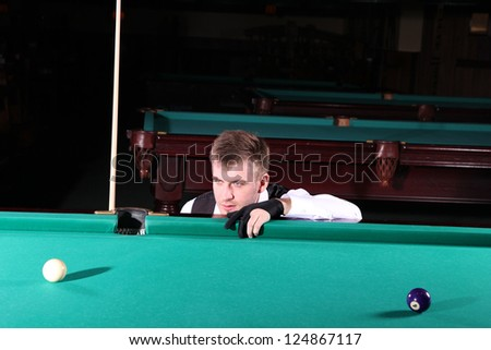 Man playing snooker in the dark club. - stock photo