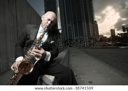 Man playing the sax downtown - stock photo