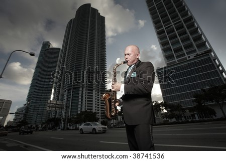 Man playing the saxophone downtown - stock photo