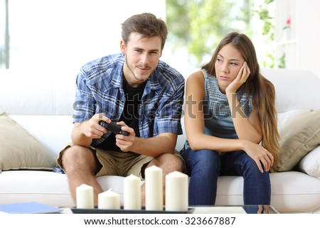 Man playing video games at home and his girlfriend bored beside looking at him - stock photo