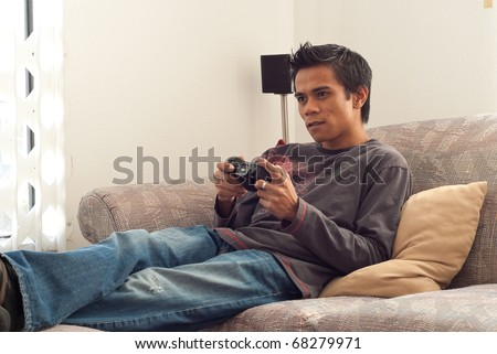 Man Playing Video Games on Couch - stock photo
