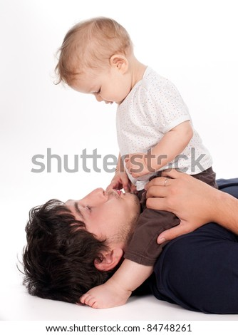 man playing with his baby on white background - stock photo