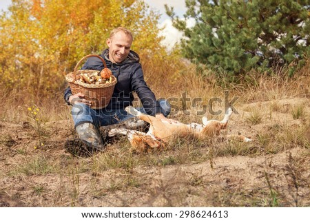 Man playing with his dog on autumn forest glade - stock photo