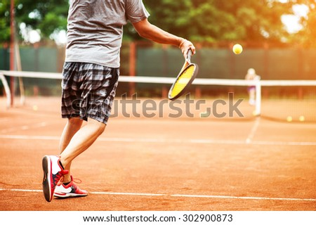 Man plays tennis and going to win against the background of the court - stock photo