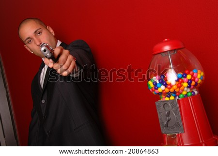 Man pointing a gun at the camera, there is a gumball machine to the right. - stock photo