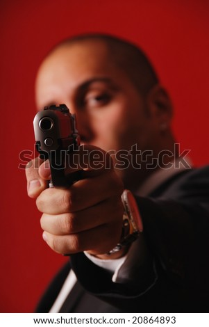 Man pointing a gun straight at the camera. Focus is on the gun. - stock photo