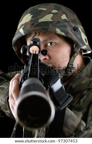 Man pointing a rifle in studio. Closeup - stock photo