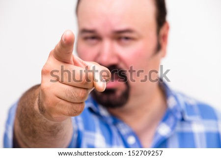 Man pointing an accusatory finger at the camera as he singles out someone to take the blame with selective focus to the hand - stock photo
